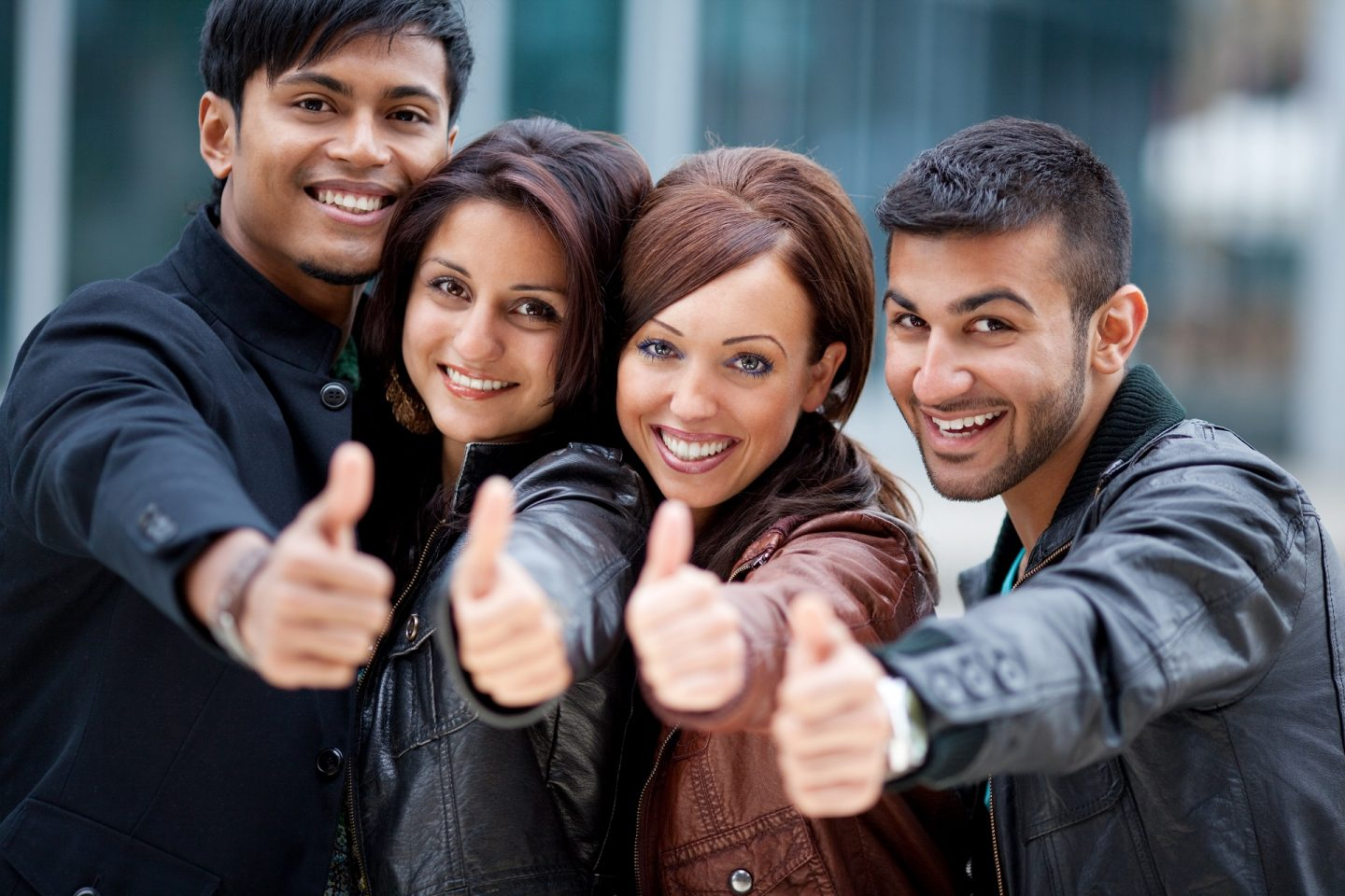 Four motivated friends giving a thumbs up